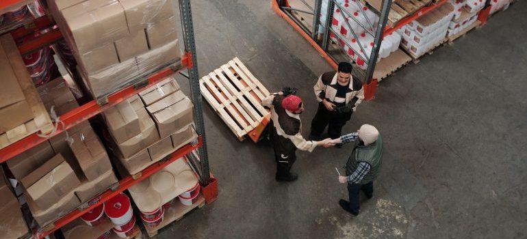 Three men talking in a storage unit