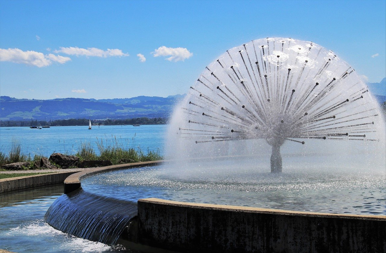 Fountain at the front with lake, a sail boat and hills on the back.