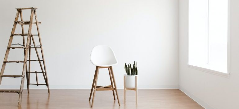 Empty room with chair, ladder and plant