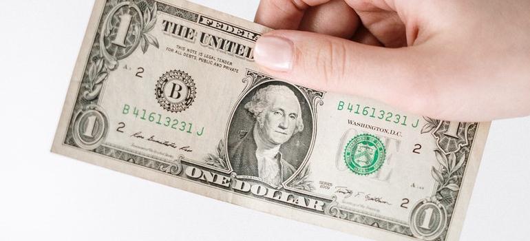 a hnad holding a dollar bill