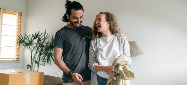 The couple is packing to move with a smile because they hired Brentford movers