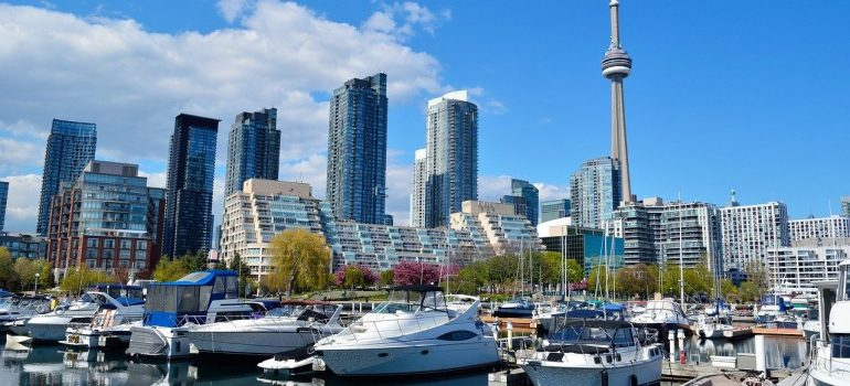A scene of Toronto, with its famous tower and high buildings on the back and a marine with boats to the front, you can visit after moving from Markham to Oakville.