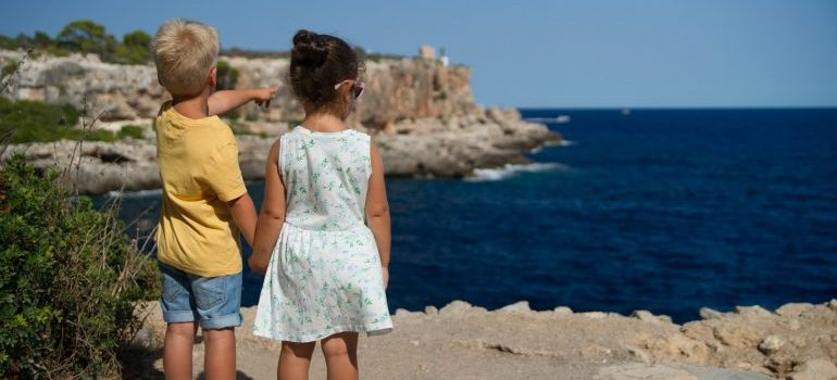 Two kids standing on the beach, watching at the sea