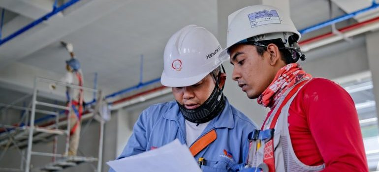 Two construction workers looking at a piece of paper