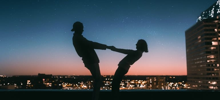 A couple dancing in front of a panorama of the city