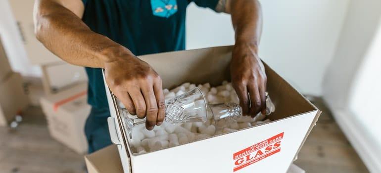 a man packing a glass item