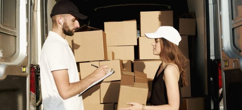 Couple talking about the average cost of moving in Toronto 2021 while packing boxes in a van