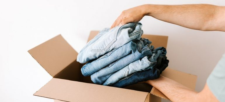 Person packing jeans into a cardboard box