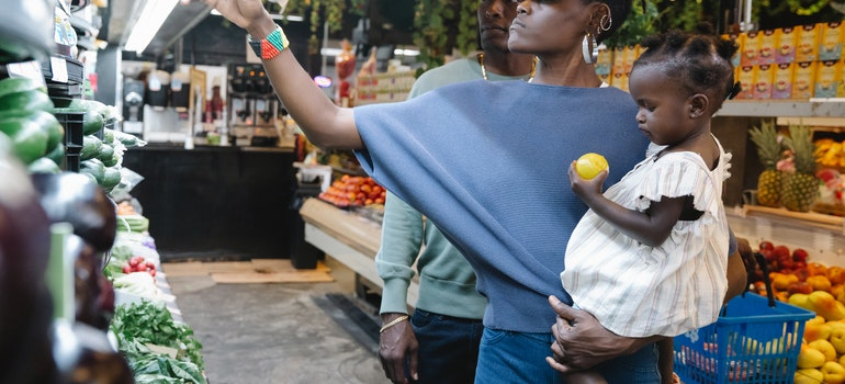 Women holding a child and doing groceries.